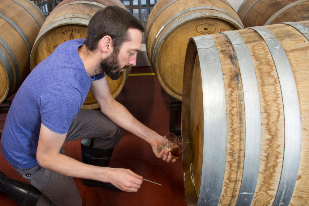 Tom Hill pulls the nail from a barrel of Bemidji's Flemish-style sour red // Photo by Brian Kaufenberg