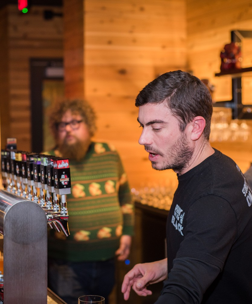Ben Smith pouring a beer behind the bar at Brewers Table // Photo by Kevin Kramer