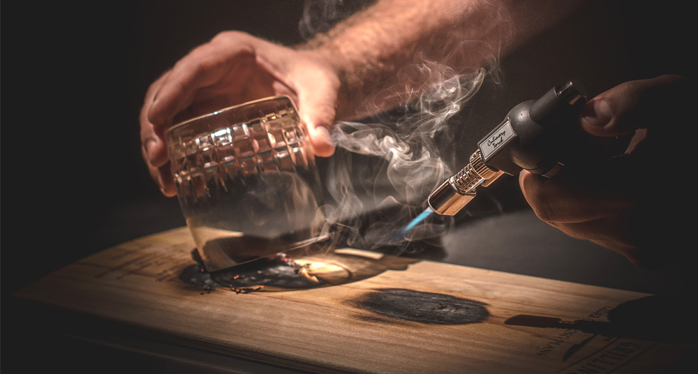 Charring a cedar grilling plank to trap the smoke in a lowball glass // Photo by Kevin Kramer, The Growler