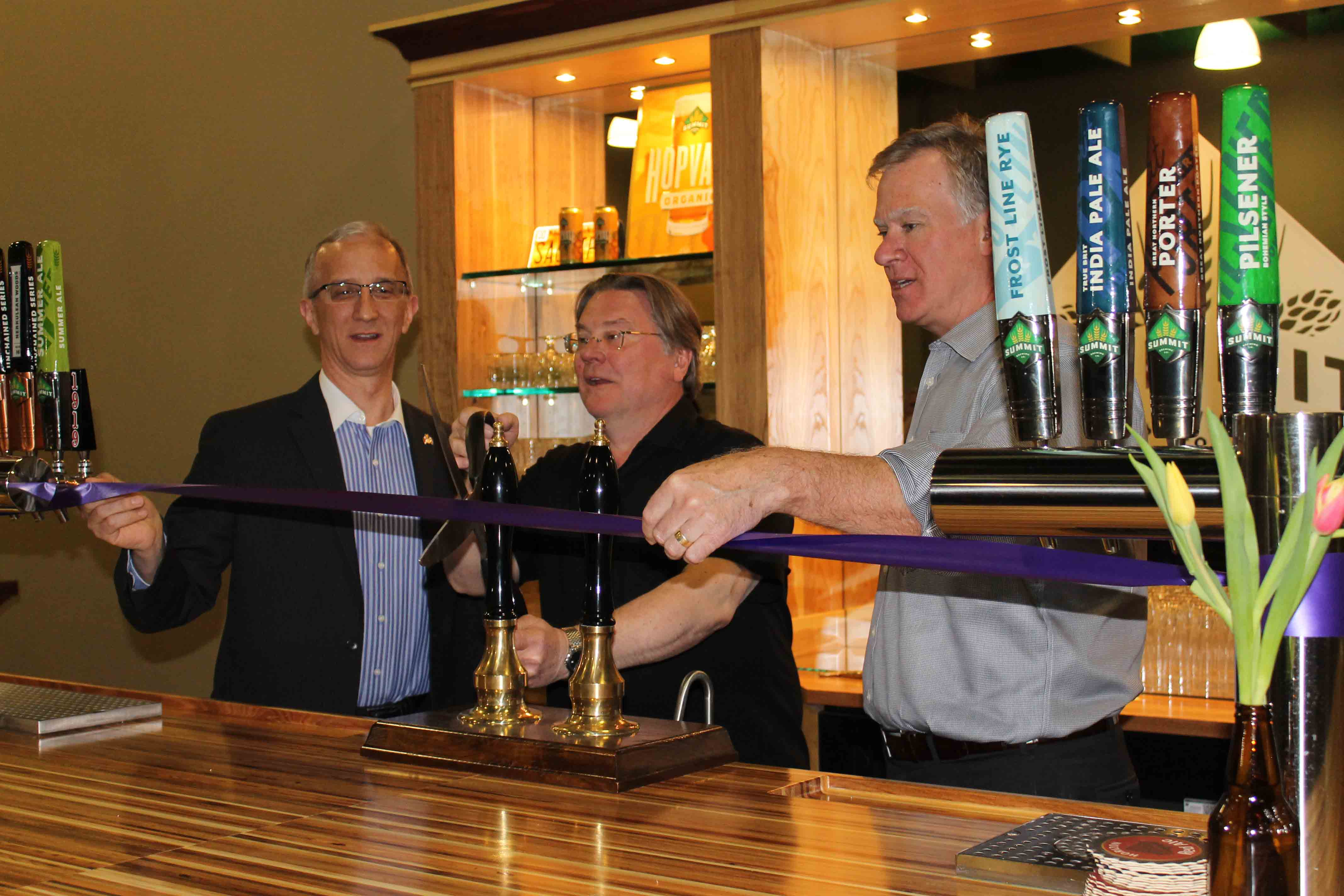 St. Paul Chamber of Commerce President Matt Kramer, Summit Brewing Company Founder and Owner Mark Stutrud and St. Paul Mayor Chris Coleman cut the ribbon on Summit's expansion facility.