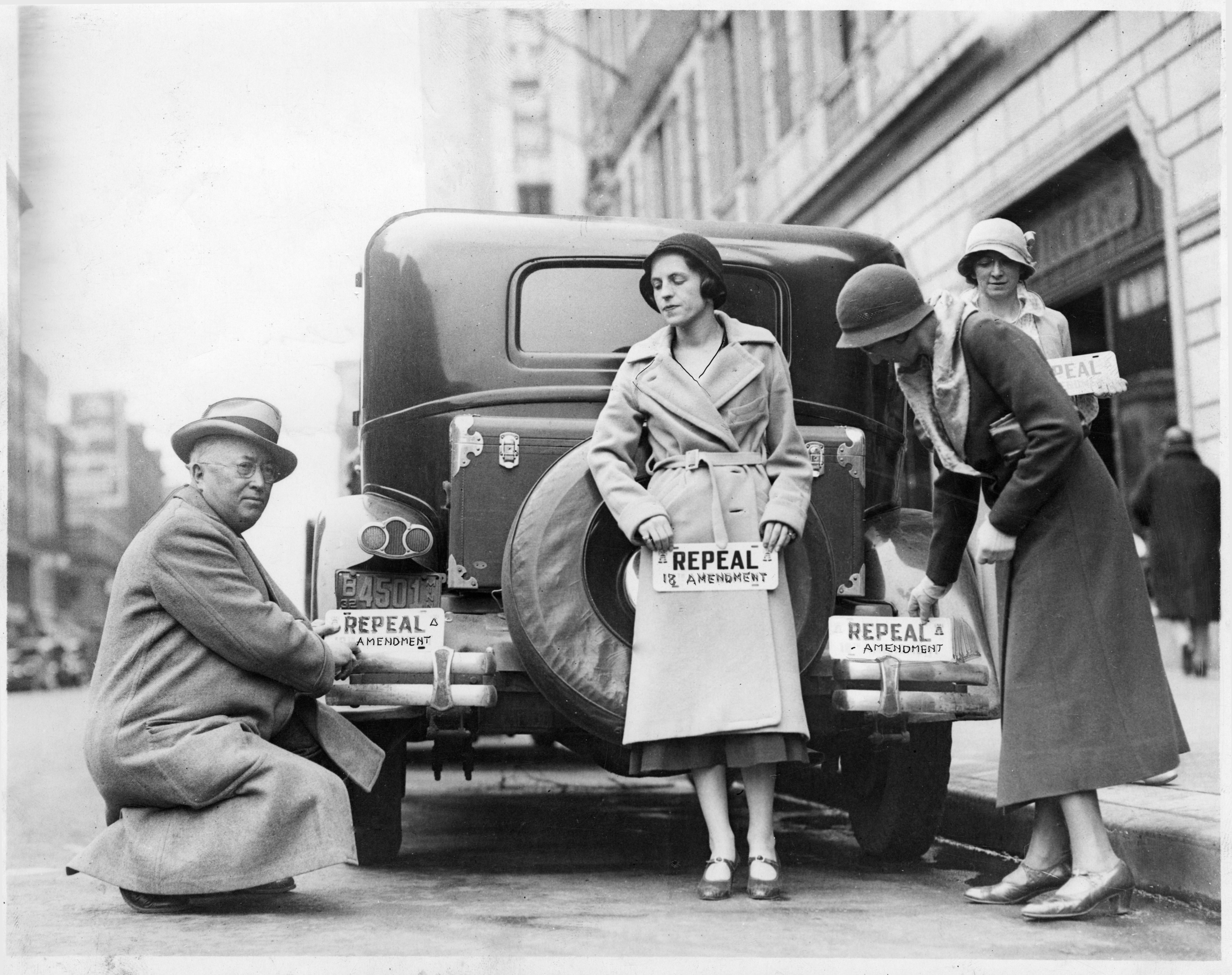 People with bumper stickers advocating the repeal of the 18th amendment (prohibition)