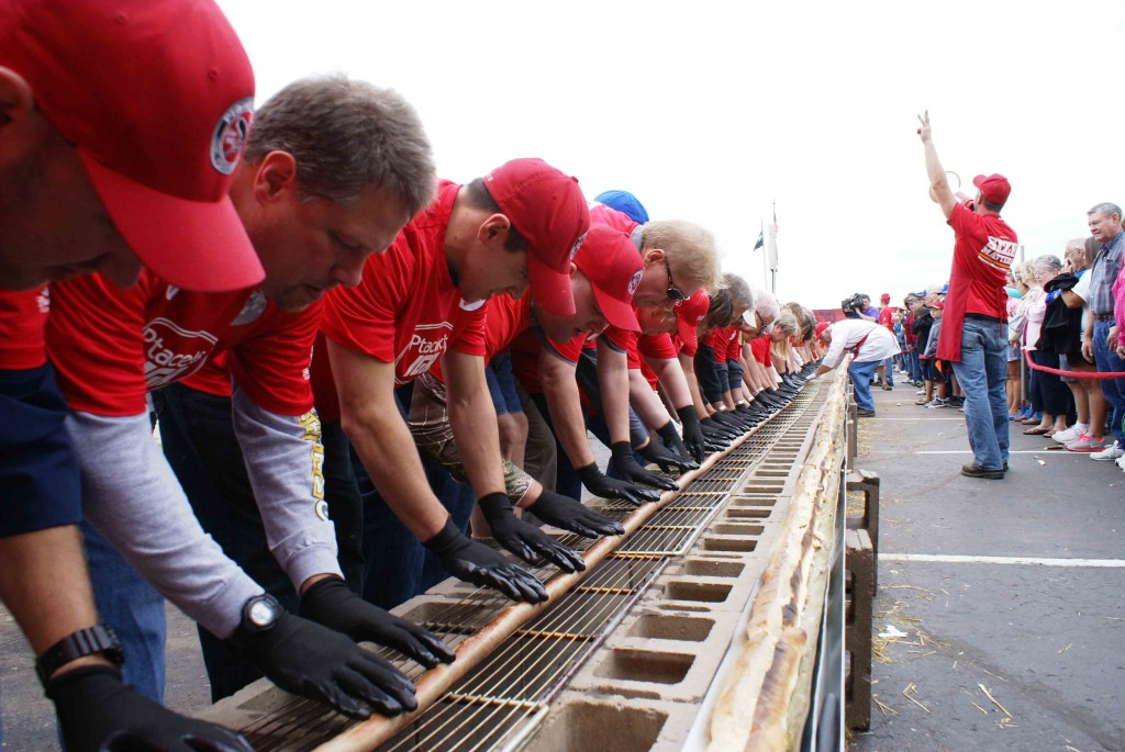 Volunteers prepare to turn a world-record breaking brat as it cooks. // Photo by Louis Garcia
