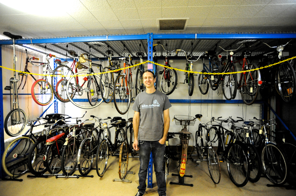 Juston Anderson standing in front of the bike collection at the Cycling Museum of Minnesota // Photo by Dan Murphy