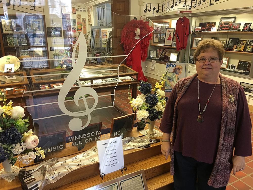Dodie Wendinger, the Executive Director of the Minnesota Music Hall of Fame, stands next to the entrance ornament - and enlarged replica of the Minnesota Music Hall of Fame award given to artists when inducted // Photo by Jay Gabler, 89.3 The Current
