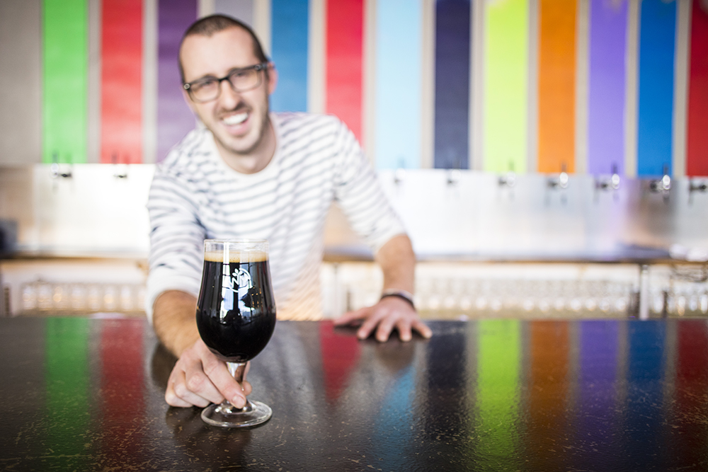 Mat Waddell pours a dark beer from the colorful taps at Wild Mind Artisan Ales // Photo by Tj Turner