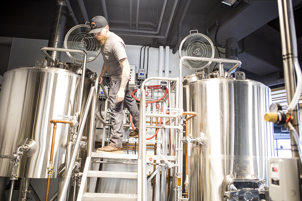 Venn brewer Ben Michaels checks in on the ongoing brews // Photo by Tj Turner