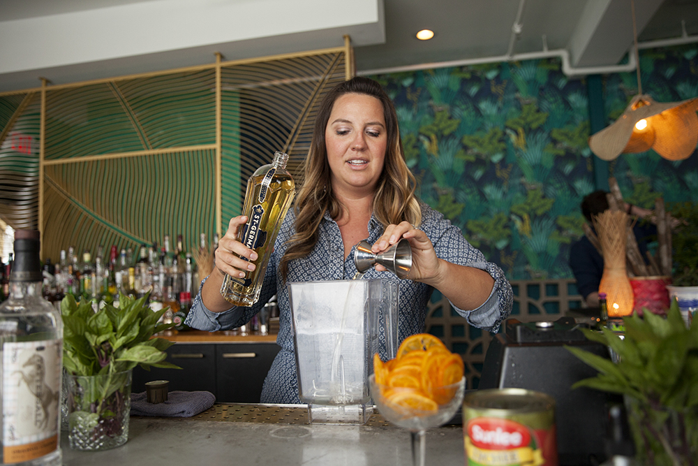 Christina Jenkins Bar Manager adding the St-Germain elderflower liqueur to the Absinthe slushie mix // Photo by Katie Cannon
