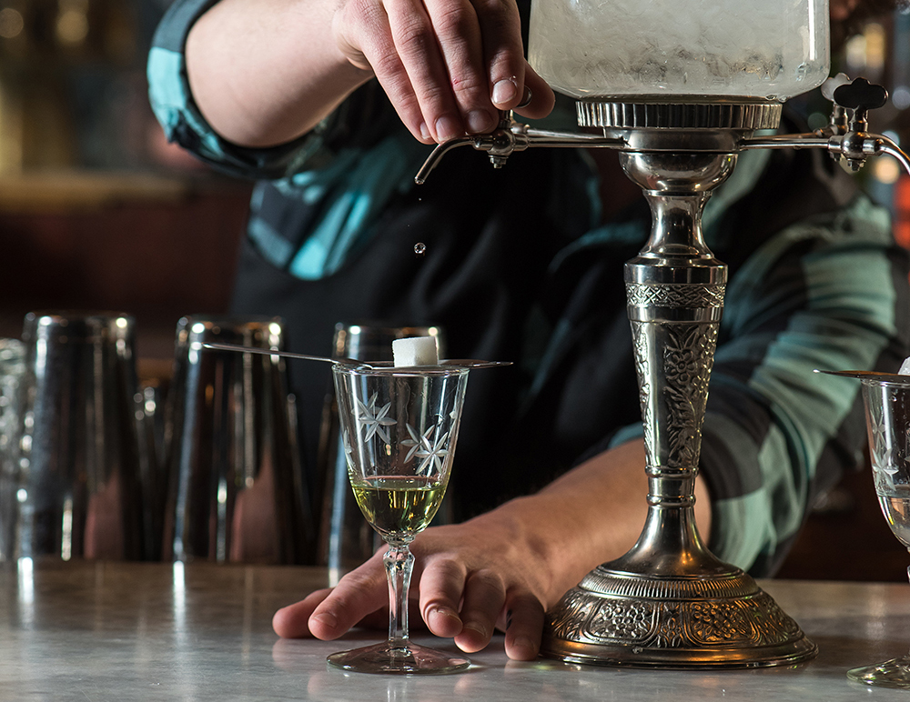 (Top) Cory Schuller fills the top of the drip with water. (Bottom) Leaving a cube of sugar on an Absinthe spoon and allowing the water to slowly drip and dissolve it into the Absinthe in the glass lets you adjust the taste of your Absinthe // Photos by Kevin Kramer