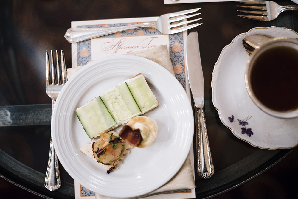 The first course of afternoon tea, a trio of canapes: cucumber slivers with benedictine on crustless brown bread, a tiny wodge of goat cheese and artichoke puff pastry and a dark fennel cracker dotted with smoked tomato aioli // Photo by Madalyn Rowell