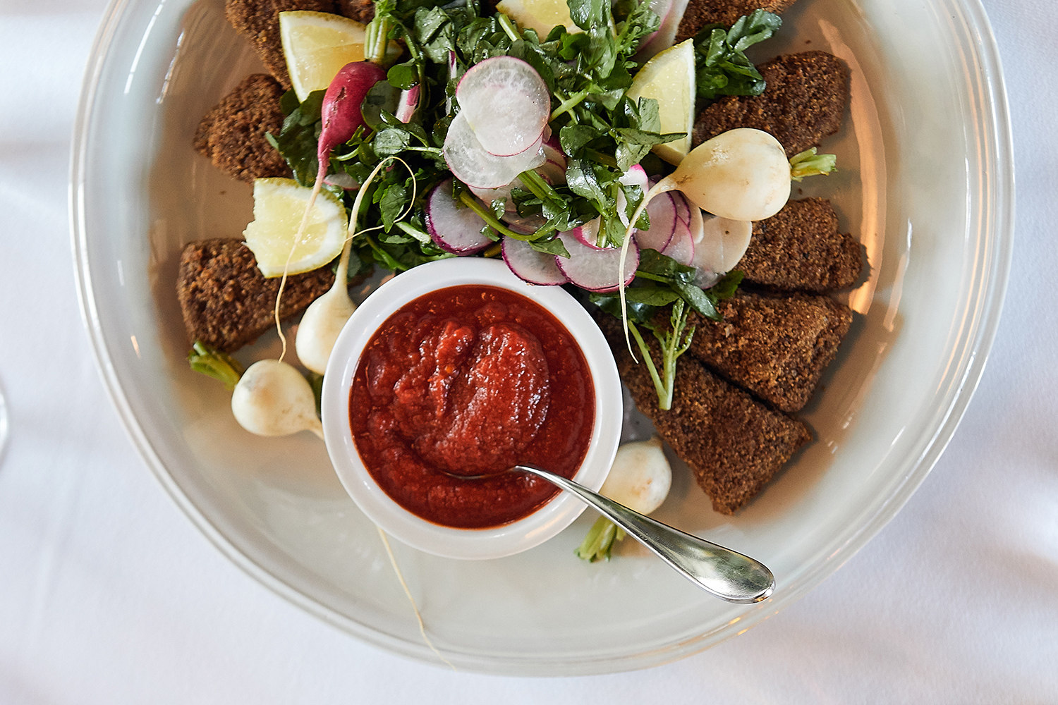Breaded goat breast cutlets, watercress salad, and spicy tomato sauce // Photo by Wing Ta