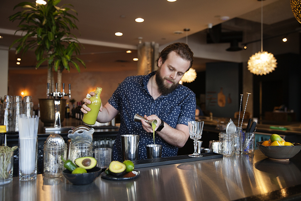 Michael Dunn pours the avocado goop into a shaker // Photo by Katie Cannon