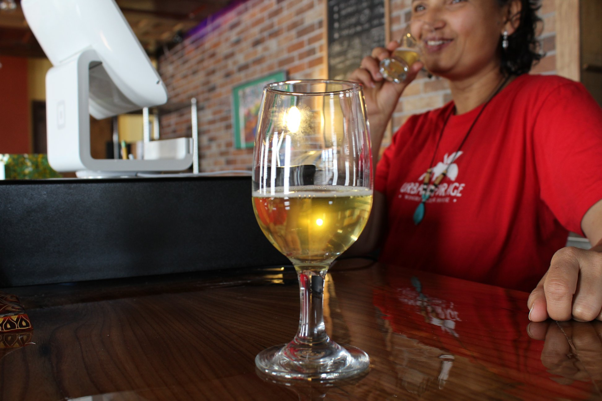 A goblet of cider at Urban Forage Winery & Cider House. Gita Zietler, an owner of Urban Forage, is in the background // Photo via Urban Forage Winery & Cider House Facebook
