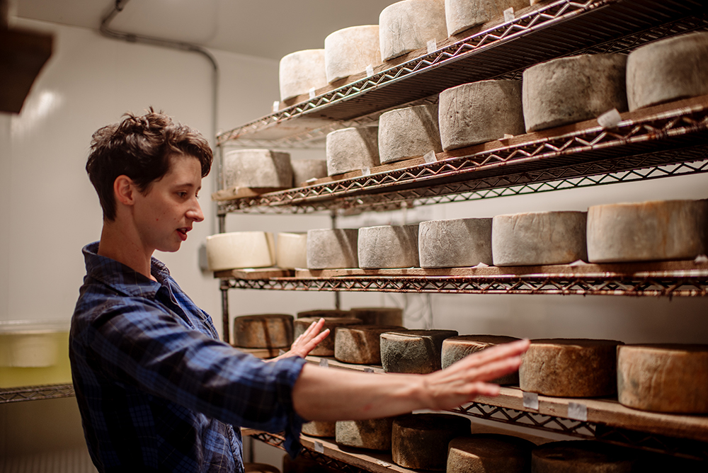 Bonow explains the cheeses aging in the storage area of Capra Nera Creamery // Photo by Becca Dilley