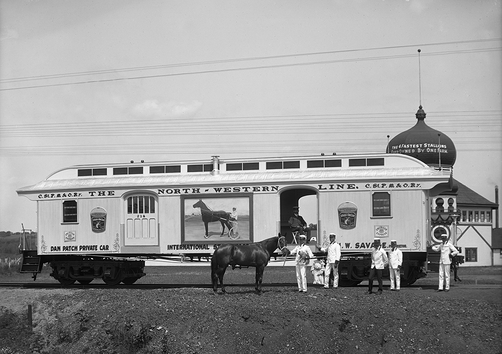 """A private car on the Dan Patch line stopped outside of the """"Taj Mahal"""" in current day Savage, Minnesota. Dan Patch stands with workers in front of the car // Photo courtesy Minnesota Historical Society"""