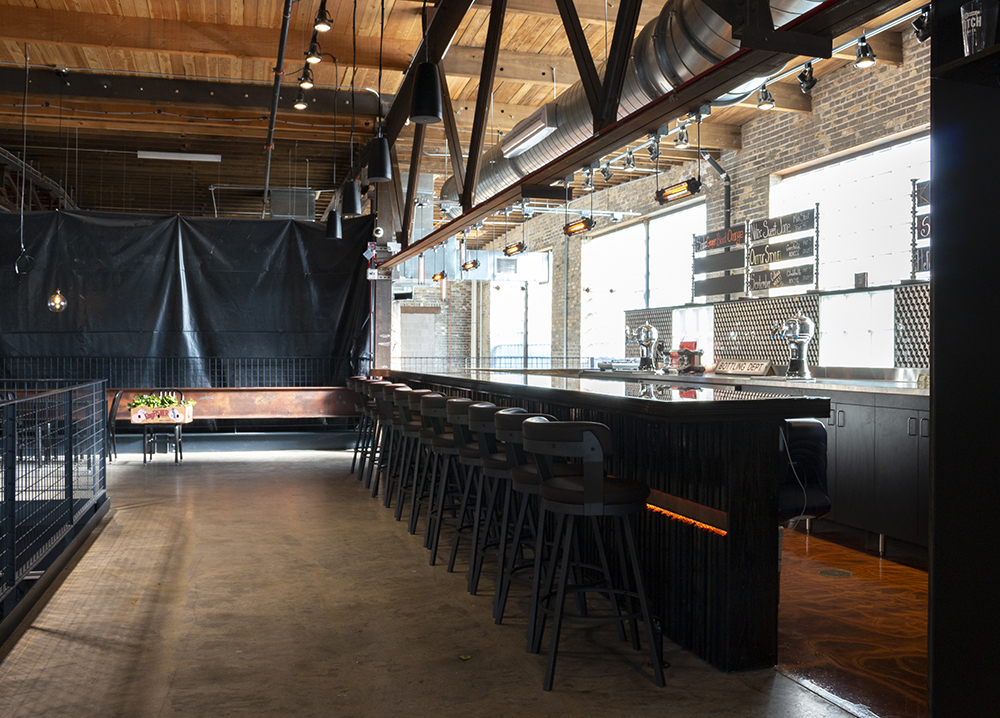The bar and brew house are on opposite sides of the mezzanine, and are split by a seating area and several other vendors // Photo by Aaron Job