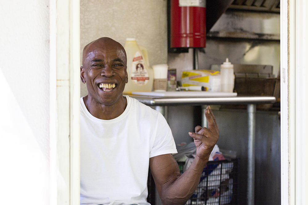 Claude Alkins smiles out of the ordering window of his food truck, which he mans alone // Photo by Aaron Job