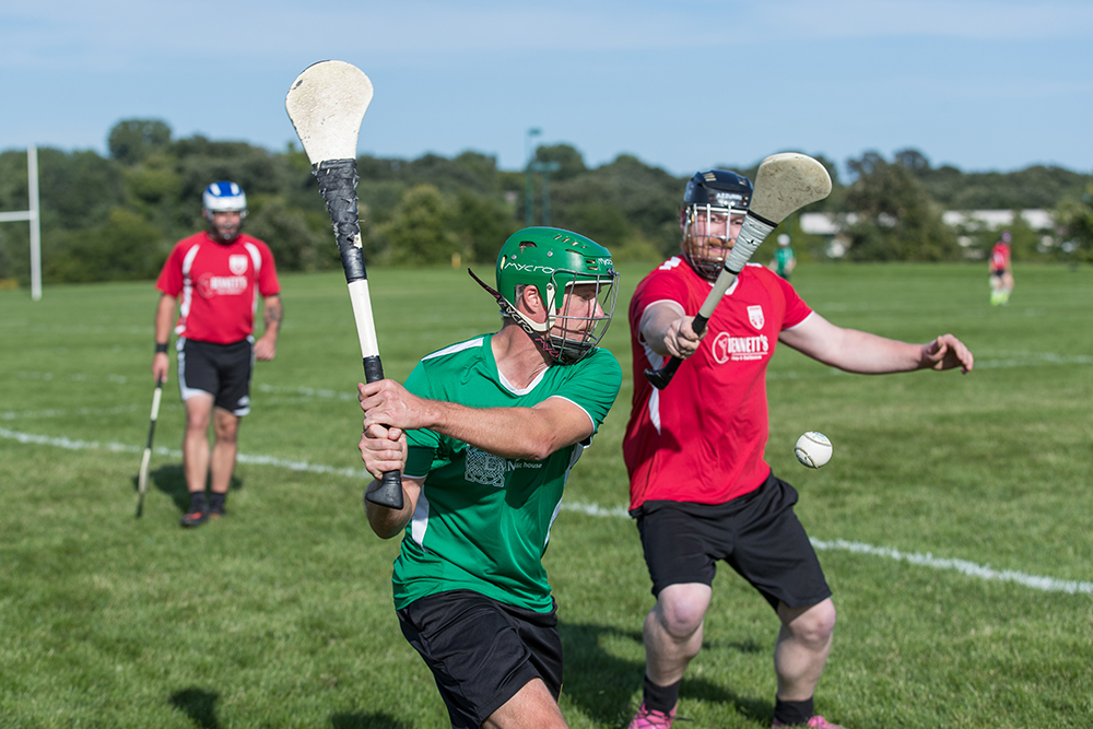 The player in green is using his hurley (stick) to try and hit the sliotar (ball) down the pitch // Photo by Ryan Siverson
