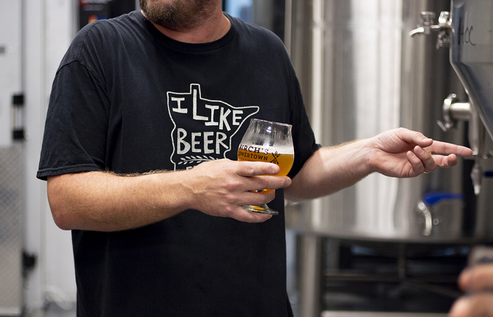 Greene holding a beer during a tour of the brewing area // Photo by Aaron Job