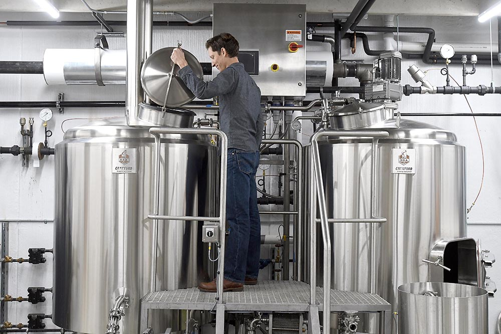 Jim examining LocAle Brewing Company's brewing equipment // Photo by Pat Christman
