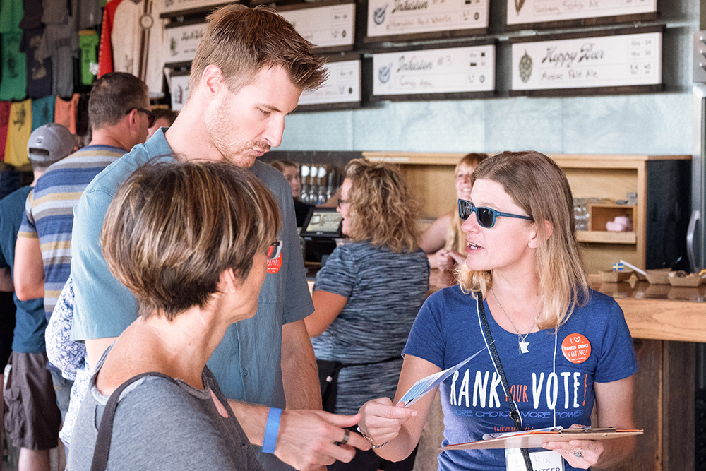 Attendees of the Best of the Wurst Festival look over the ranked voting choices // Photo courtesy FairVote Minnesota