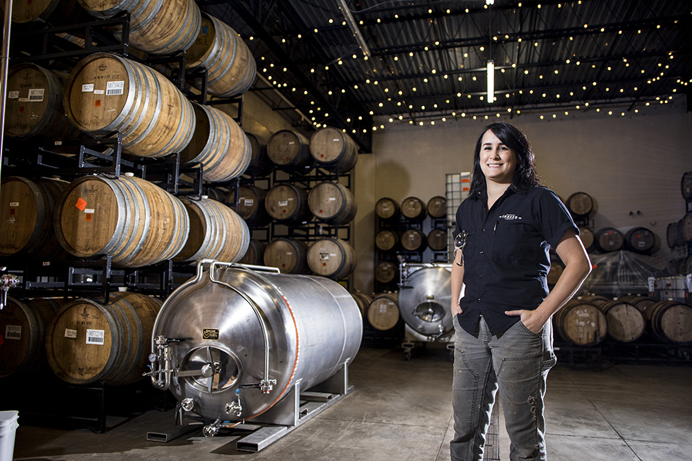 Tina Spurr with the barrels at Indeed Brewing Company // Photo by Tj Turner