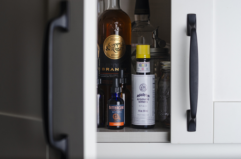 A cabinet filled with bitters and cocktail essentials // Photo by Aaron Job