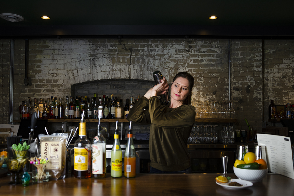 Jami Olson shaking her bourbon sour behind the bar at Popul Vuh // Photo by Aaron Job