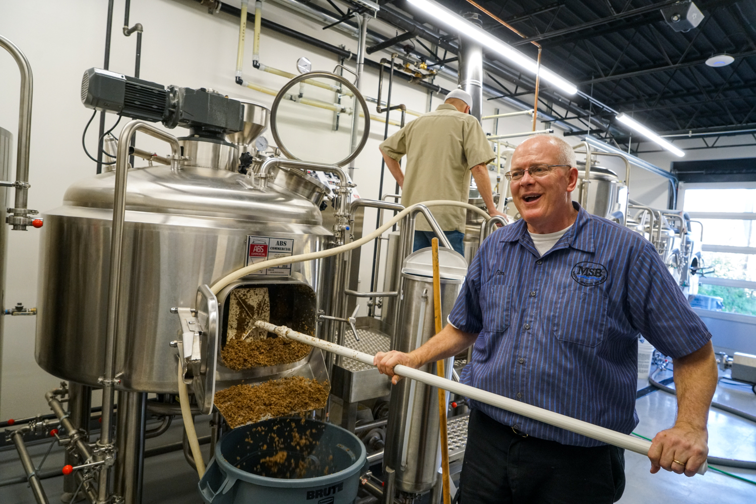 Tim Pelton scoops spent grain from Mineral Springs Brewery's brewing system // Photo by James Figy