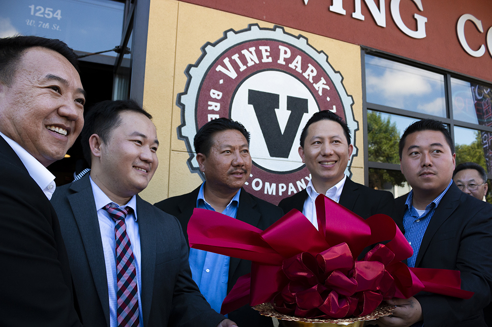 The new owners of Vine Park Brewing Company, from left to right, Nhiasing Moua, Jai Fang, Touyer Moua, and Tou Thao, (with community member right) holding the ceremonial ribbon outside of Vine Park on 7th Street West in St. Paul, Minnesota // Photo by Aaron Job