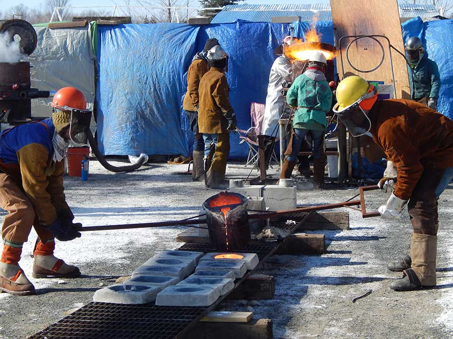 Franconia artists, all experienced metal casters, pour molten iron into molds made by community members // Photo courtesy Franconia Sculpture Park