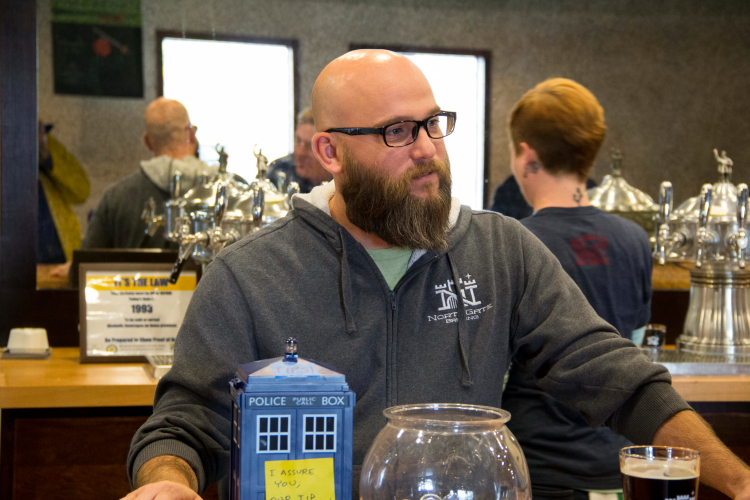NorthGate Brewing co-owner and co-founder Adam Sjogren behind the taproom bar // Photo by Brian Kaufenberg