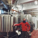 Bemidji Brewing's Tom Hill in front of the brewery's new 15-barrel brewing system // Photo via Bemidji Brewing's Facebook