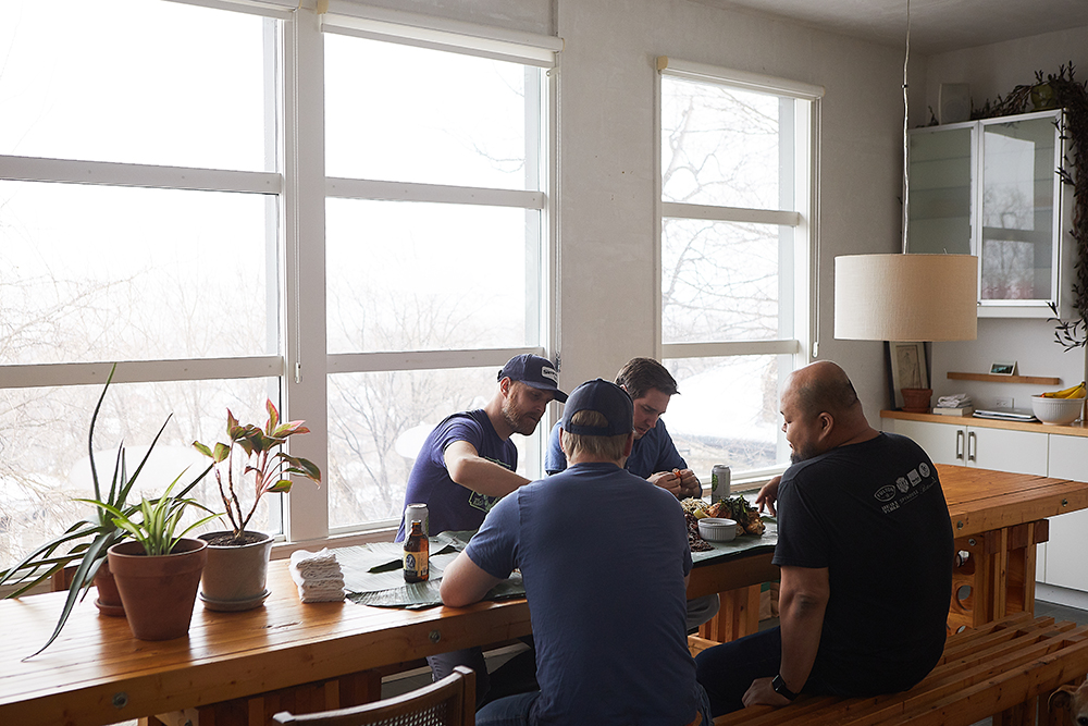 Editor-In-Chief Joe Alton, left, The Growler's Senior Editor John Garland, back, Yia Vang, right, and Jon Wipfli, front, enjoying the meal // Photo by Wing Ta