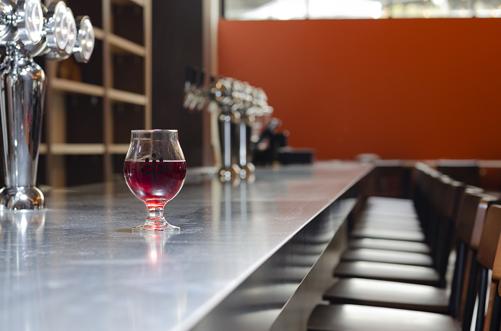 A glass of Black Market, the rebranded version of Number 12's Black Currant Dry, sits on the bar of the cidery's new North Loop taproom // Photo by Aaron Job