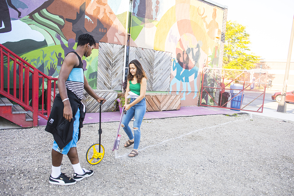 Two JXTA Art students mark the outline of the youth-designed art plaza and skatepark in North Minneapolis // Photo by Tj Turner