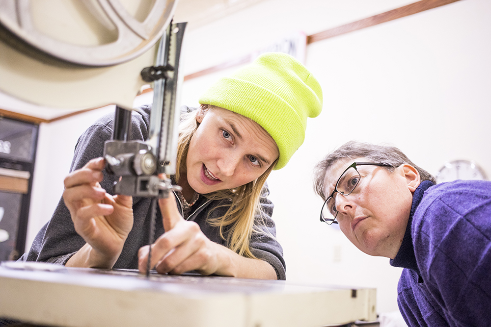 Jess Hirsch, left, inspects the blade of a band saw at Women's Woodshop // Photo by Tj Turner
